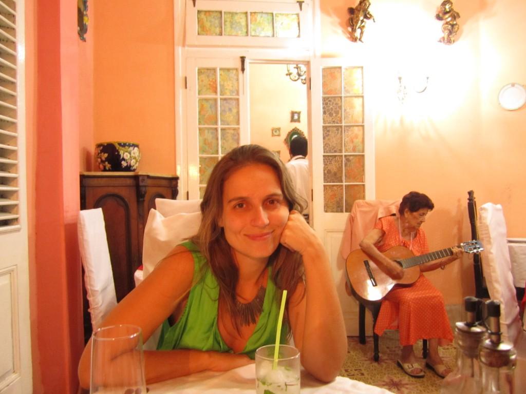 Eu (cansada depois de 200 horas de voo, mas feliz) em um paladar na primeira noite em Cuba. E o charme da tiazinha tocando música cubana ao fundo?!
