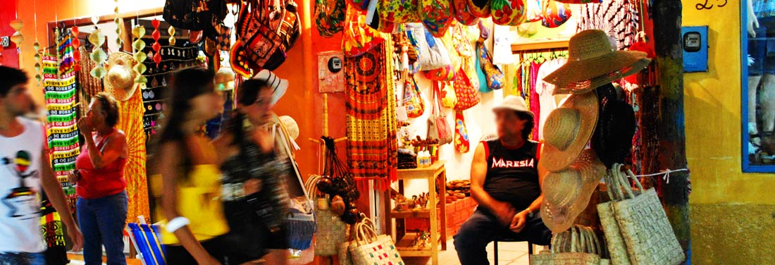 Noite na Rua Broduei de Arraial, com pedestres passando pelas lojinhas.