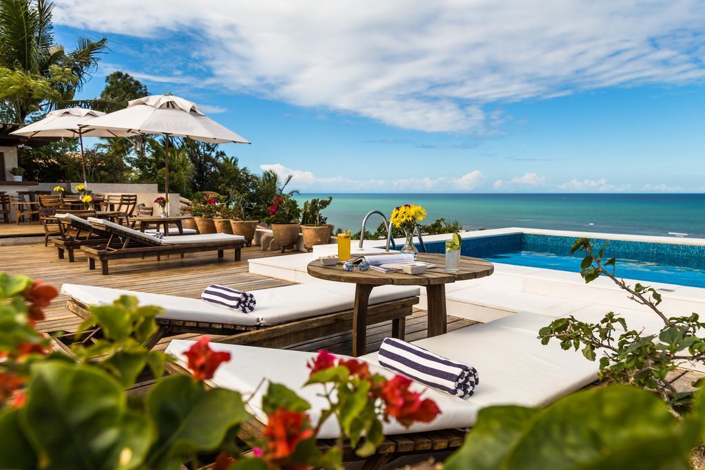 Espreguiçadeiras na piscina do hotel Maitei, com mar ao fundo.