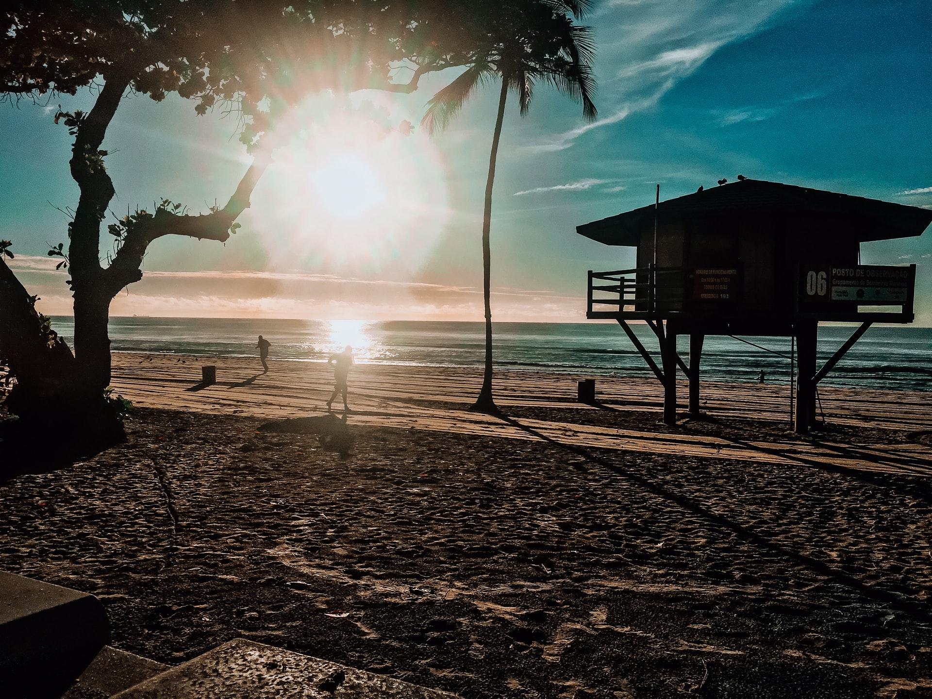 Amanhecer na praia de Boa Viagem, em Recife. Duas pessoas se exercitando na orla, um quiosque à direita e uma árvore à esquerda.