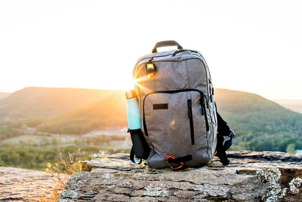 Mochila para trilhar montanhas sobre uma pedra e com uma montanha ao fundo